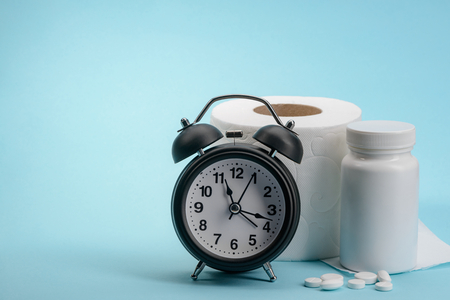 Alarm clock, toilet paper and medicine on blue background. Laxative pills commercial concept.