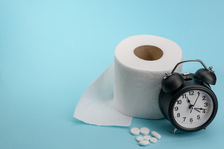 Toilet paper, pills and alarm clock on blue background. Diarhhea or constipation cure. Medical commercial concept.