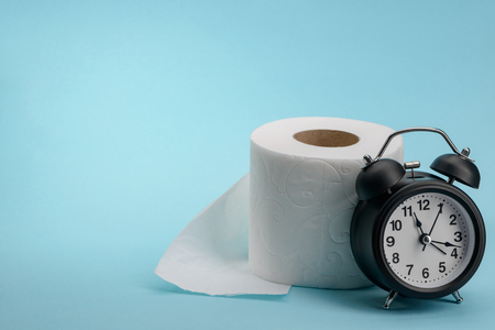 Toilet paper roll and alarm clock on blue background with copy space. Digestion problem concept. Imagens