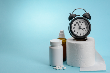 Toilet paper, medicine drugs and clock on blue background with copy space. Fast and efficient treatment of digestive disorders.