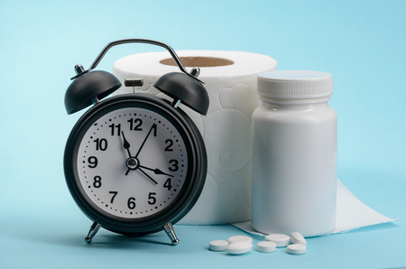 Alarm clock, toilet paper and laxative pills on blue background. Fast and efficient treatment for constipation.