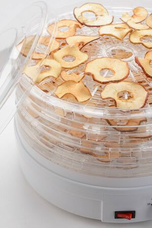Dried apple chips in a dehydrator. Making chewy and crispy fruit snacks at home with a special kitchen equipment. Imagens