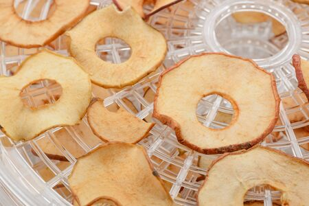 Close-up on dried apple slices. Cut fruits spread on a reck of a dryer. Source of vitamins and nutrients. Imagens