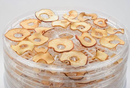 Dried apple rings on a dryer rack, close-up. Perfect fruit snack without added sugar, made at home. Imagens
