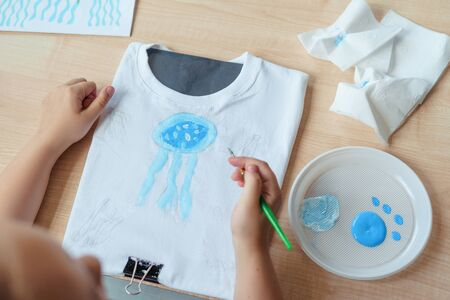 Child painting a blue jellyfish