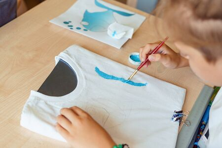 Child painting on white t-shirt