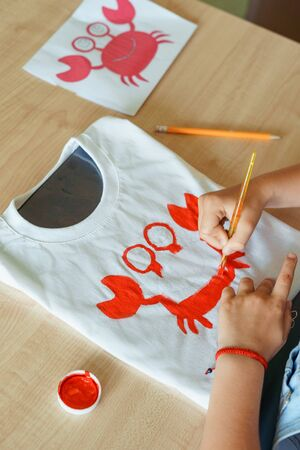 Child painting a red crab