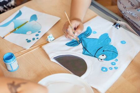 Child painting a blue fish