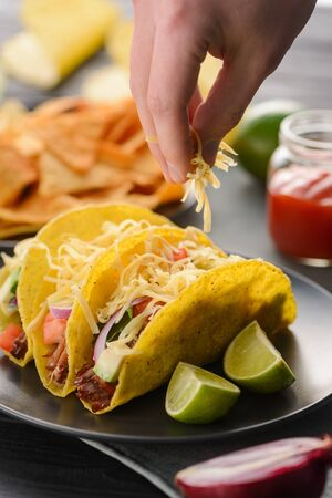 Hand sprinkles cheese onto tacos