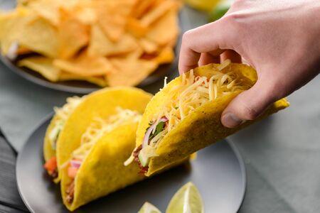 Hand grabbing a taco shell