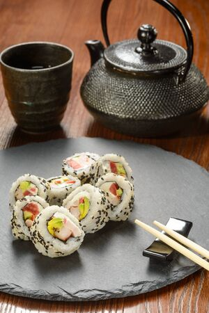 Sushi rolls and cast-iron cup