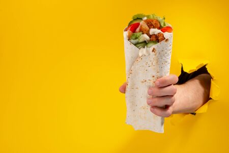 Hand giving a doner roll