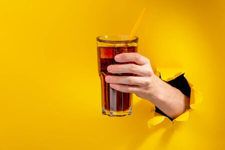 Hand holding a glass of cola with a straw. Hand offering the drink through a torn hole in yellow paper background. Reklamní fotografie