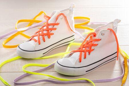Weiße Sneaker mit Gitterschnürung. Orange, gelbe und violette Schnürsenkel, um Ihre Schuhe stilvoll aussehen zu lassen.