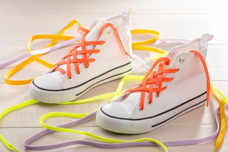 White sneakers with lattice lacing. Orange, yellow and violet shoelace to make your shoes look stylish.