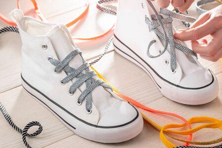 Nahaufnahme auf Turnschuhen, die geschnürt werden. Kreative Art, Ihre Schuhe mit bunten Schnürsenkeln schick aussehen zu lassen. Standard-Bild