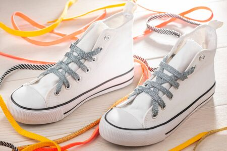 White sneakers with silver shoelaces on wooden background. Beautifully laced up shoes.