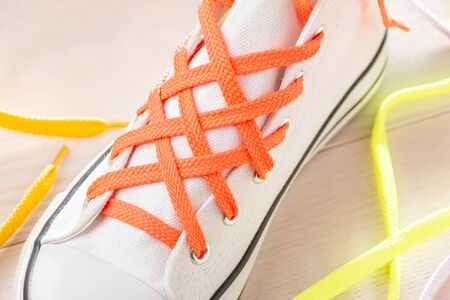 Close-up shot of lattice lacing. White sneaker tied with orange shoelaces in a creative way. 版權商用圖片