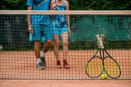 Low shot of athletes getting towards the net to take their rackets and balls. Banco de Imagens