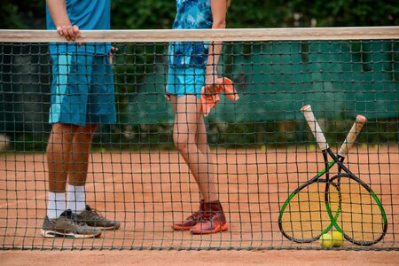 Couple of players having a break, standing near the net.