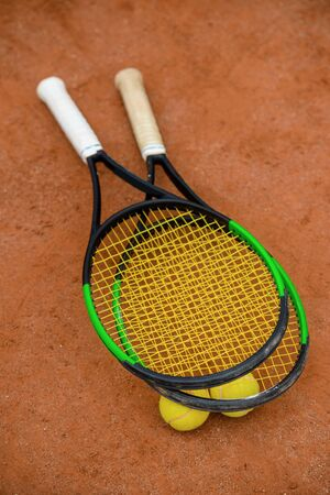 Tennis rackets and balls on the ground of an outdoor court.