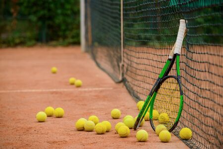 Tennis rackets and plenty of balls on the ground