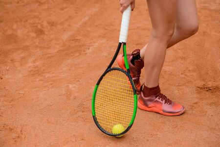 Woman holding a tennis racket near the ground, low section shot.