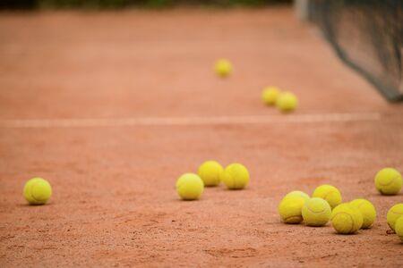 Plenty of tennis yellow balls on the ground of outdoor court.