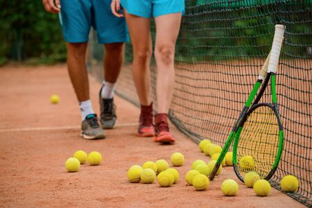 Plenty of balls laying on a outdoor court and two rackets.