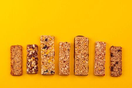 Row of different granola bars on yellow background Banco de Imagens