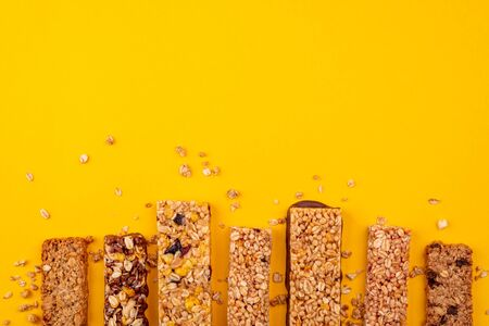 Row of delicious granola bars on yellow background