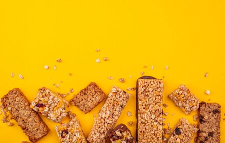 Assorted granola bars with crumbs on yellow background