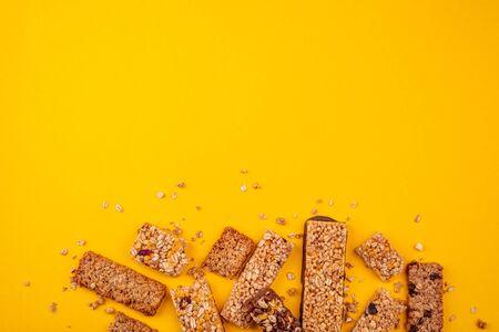 Heap of broken granola bars on yellow background