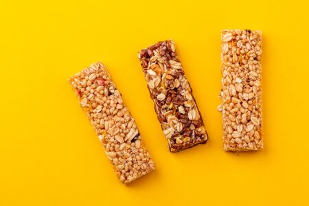 Top view on three granola bars on yellow background