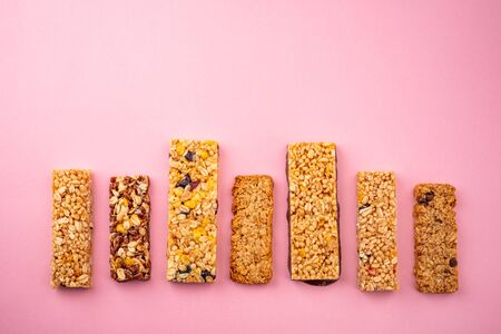 Row of different granola bars on pink background