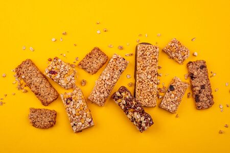Top view on various granola bars on yellow background Banco de Imagens