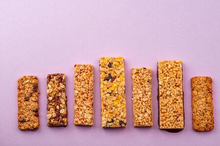 Row of different granola bars on violet background Banco de Imagens
