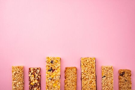Row of assorted granola bars on pink background