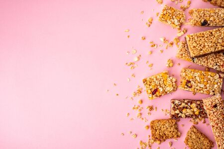 Crumbs and pieces of granola bars on pink background Banco de Imagens