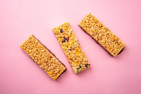 Top view on three granola bars on pink background Banco de Imagens