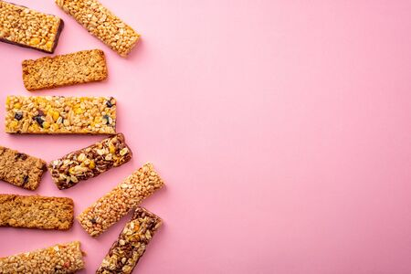 Assorted granola bars on pink background with copy space