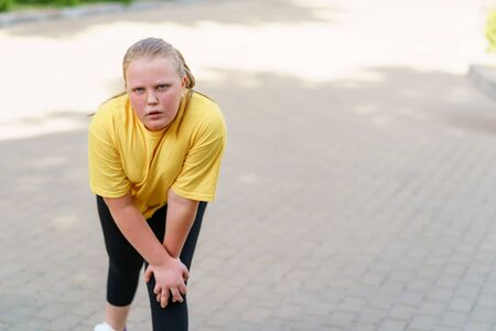 Exhausted overweight girl resting after intensive exercises. Stock Photo
