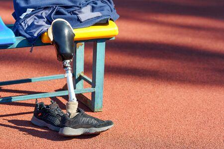 Sneakers en verwijderde prothetische benen bij de stoel in een stadion. Stockfoto