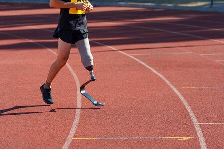 Man with prosthetic leg running at a stadium