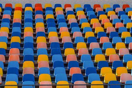 Sièges en plastique de stade bleu et orange. Texture colorée, rangées d'une arène.