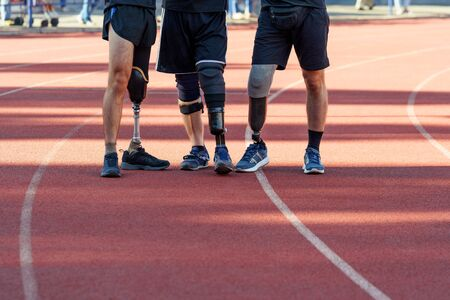 Three amputee sportsmen standing on a track, low-section shot.