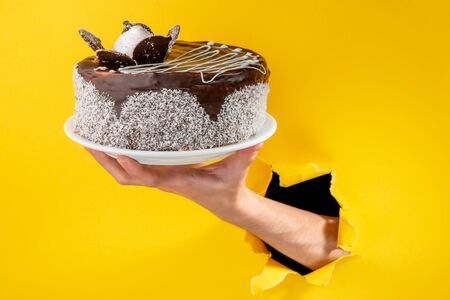 Hand holding a chocolate cake through a torn hole in yellow paper background