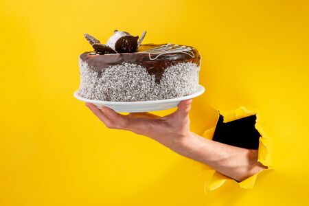 Hand serving a chocolate cake through a torn hole in yellow paper background