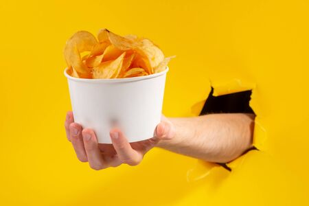 Hand holding a cup of potato chips through a torn hole in yellow background.
