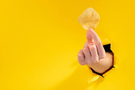 Hand holding a potato chip through paper background with copy space.